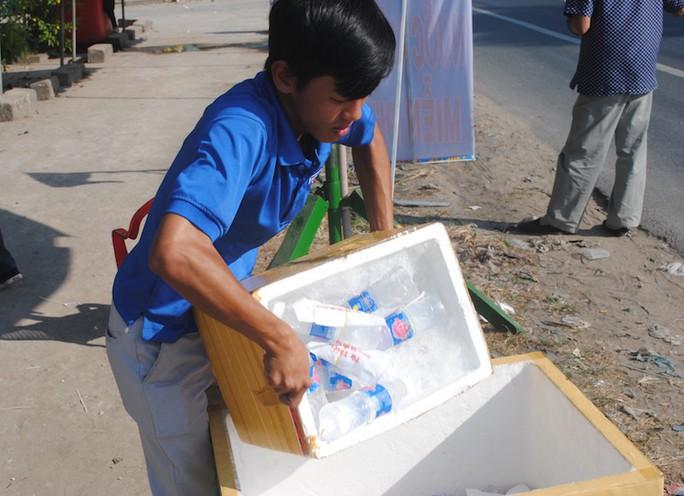CSGT Đồng Tháp phát nước, khăn lạnh cho người dân trên đường về quê ăn Tết - Ảnh 1.