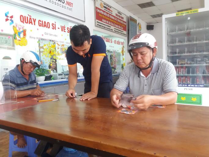 Tranh nhau mua vé số cào trúng độc đắc 300 triệu đồng ngày 30 Tết - Ảnh 1.