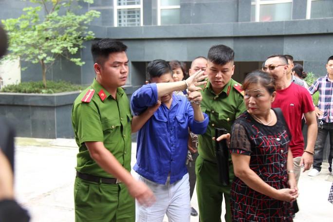 Ông trùm Hưng kính liên tục lấy tay che mặt, tránh ống kính phóng viên khi ra tòa - Ảnh 2.