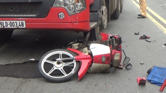 Xe máy cùng người đàn ông bị xe container cuốn vào gầm và kéo lê trên đường - Ảnh 1.