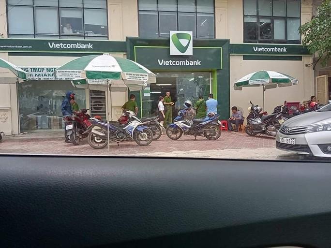 Kẻ bịt mặt cầm súng xông vào uy hiếp nhân viên, cướp ngân hàng Vietcombank - Ảnh 1.