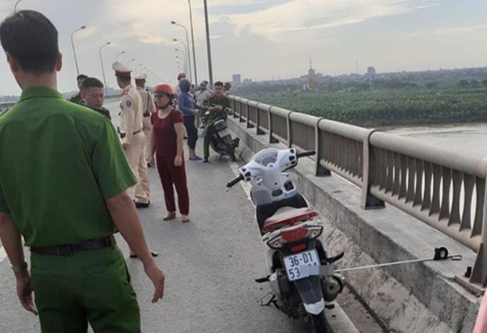 Bỏ lại xe máy trên cầu, cô gái trẻ bất ngờ nhảy xuống sông Hồng tự tử - Ảnh 1.