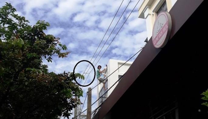 Thợ sơn liều lĩnh buộc 3 dây điện trung thế để tiện sơn vôi mặt tiền - Ảnh 1.