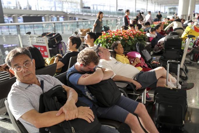 Sân bay Hồng Kông mở cửa trở lại, hàng ngàn người vẫn mắc kẹt - Ảnh 1.