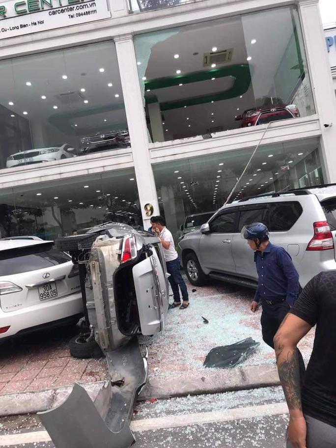 Xe Vios bất ngờ lao từ tầng 2 showroom xuống đất, rơi trúng xe Toyota Prado - Ảnh 1.