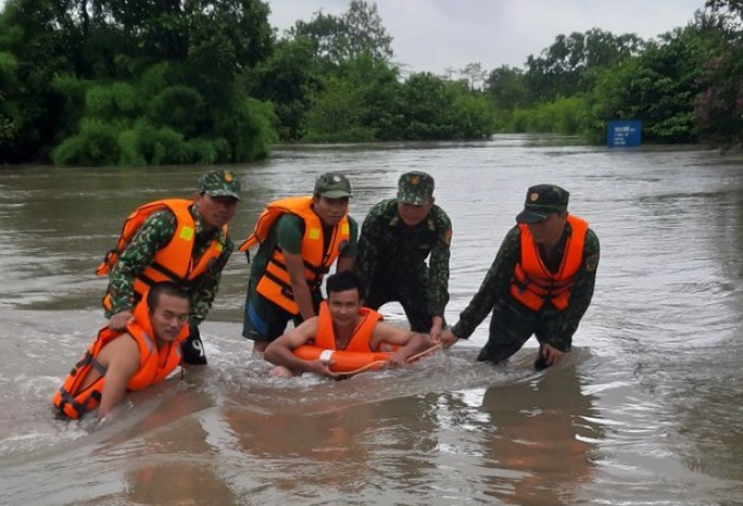 Cứu 3 người dân mắc kẹt trong dòng nước lũ - Ảnh 1.