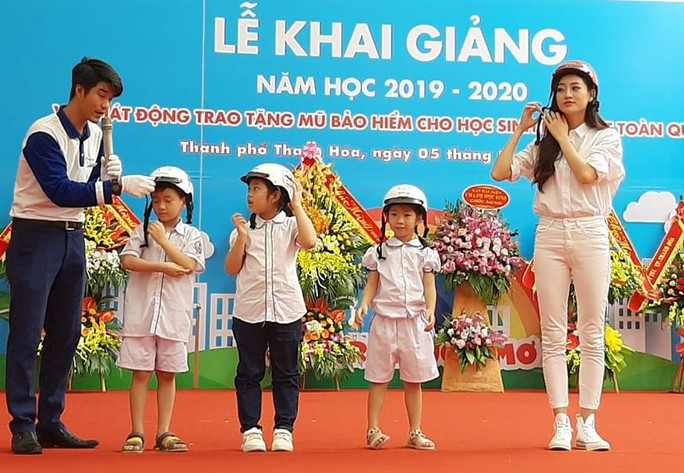 Hoa hậu Lương Thùy Linh trao mũ bảo hiểm cho học sinh trong ngày khai giảng - Ảnh 1.