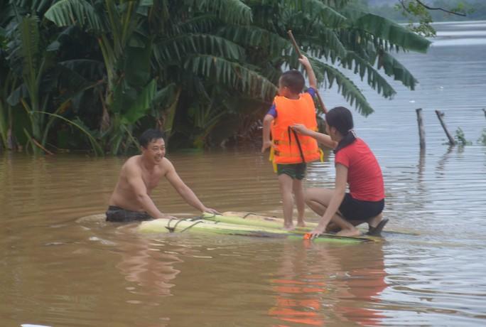Người dân làm bè chuối để đưa các cháu nhỏ qua lại trên dòng nước