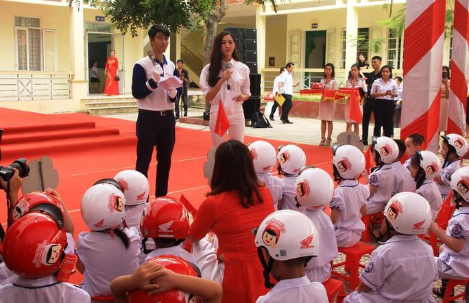 Hoa hậu Lương Thùy Linh trao mũ bảo hiểm cho học sinh trong ngày khai giảng - Ảnh 8.