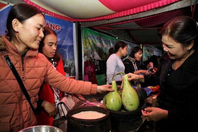 Chủ gian hàng giới thiệu nông sản cho khách tại phiên chợ