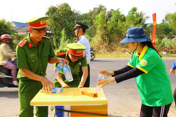 Mát lòng những chai suối lạnh của công an tặng người dân về quê ăn Tết - Ảnh 1.