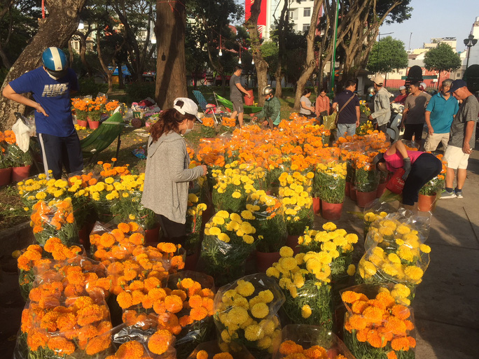Chen nhau mua hoa giảm giá sáng 30 Tết, hàng chục gốc đào xứ Bắc bị bỏ lại ở chợ hoa - Ảnh 1.