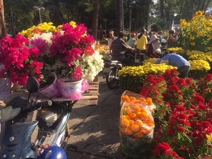 Chen nhau mua hoa giảm giá sáng 30 Tết, hàng chục gốc đào xứ Bắc bị bỏ lại ở chợ hoa - Ảnh 2.