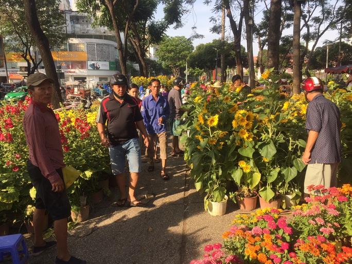 Chen nhau mua hoa giảm giá sáng 30 Tết, hàng chục gốc đào xứ Bắc bị bỏ lại ở chợ hoa - Ảnh 3.