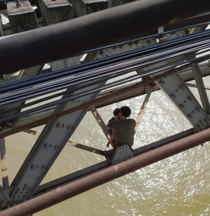 Thanh niên buồn chuyện gia đình ôm con nhỏ ngồi vắt vẻo trên thanh giằng cầu Long Biên - Ảnh 1.