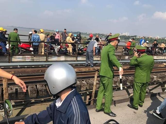 Thanh niên buồn chuyện gia đình ôm con nhỏ ngồi vắt vẻo trên thanh giằng cầu Long Biên - Ảnh 2.