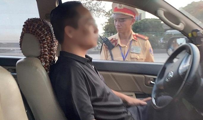 Bị thổi nồng độ cồn, tài xế cố thủ trong xe ôtô 3 giờ và liên tục uống nước - Ảnh 1.