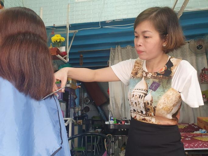 Người phụ nữ hớt tóc điêu luyện bằng một tay - Ảnh 1.