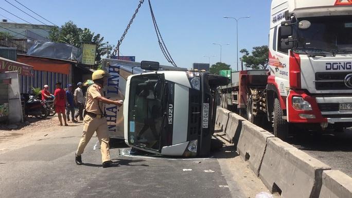 Xe tải tông dải phân cách, văng qua làn đường xe máy gần cầu vượt Sóng Thần - Ảnh 1.