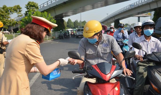 Giữa trưa, CSGT phát khẩu trang y tế cho người dân ở cửa ngõ Tân Sơn Nhất - Ảnh 5.
