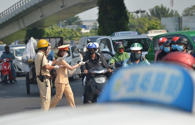 Giữa trưa, CSGT phát khẩu trang y tế cho người dân ở cửa ngõ Tân Sơn Nhất - Ảnh 4.