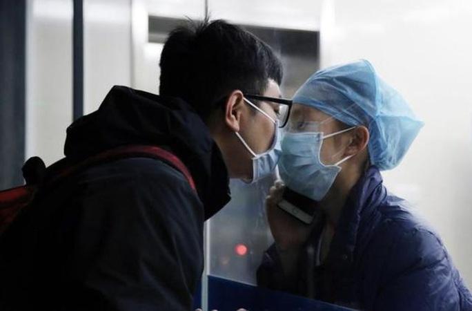 Giữa đại dịch virus corona, nữ y tá hôn bạn trai qua tấm kính cách ly - Ảnh 1.