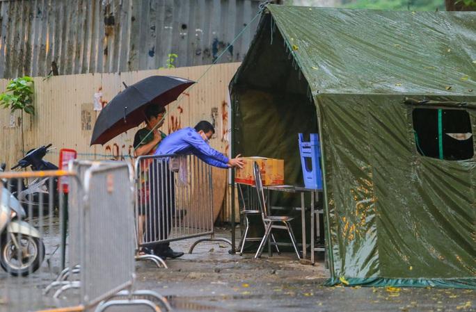 CLIP: Thân nhân đội mưa tiếp tế cho người trong khu cách ly vì Covid-19 - Ảnh 2.