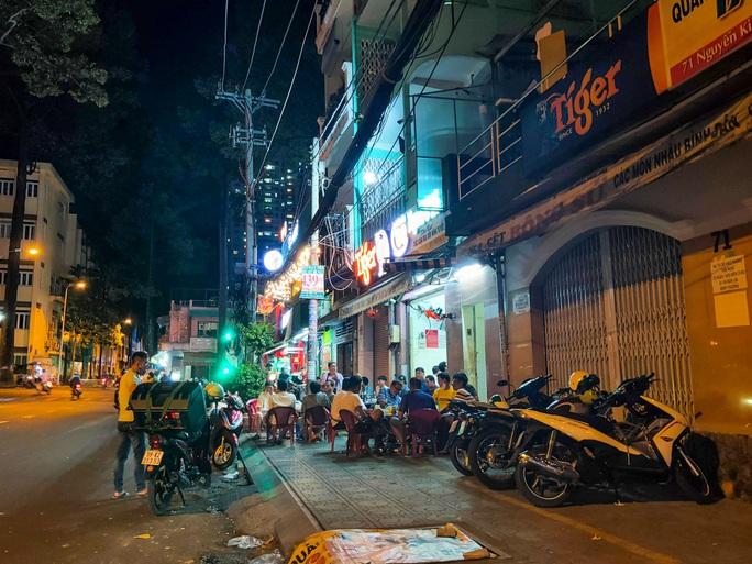 Sau giờ G, hàng quán trung tâm TP HCM đóng cửa, nhiều nơi khác vẫn tưng bừng - Ảnh 9.