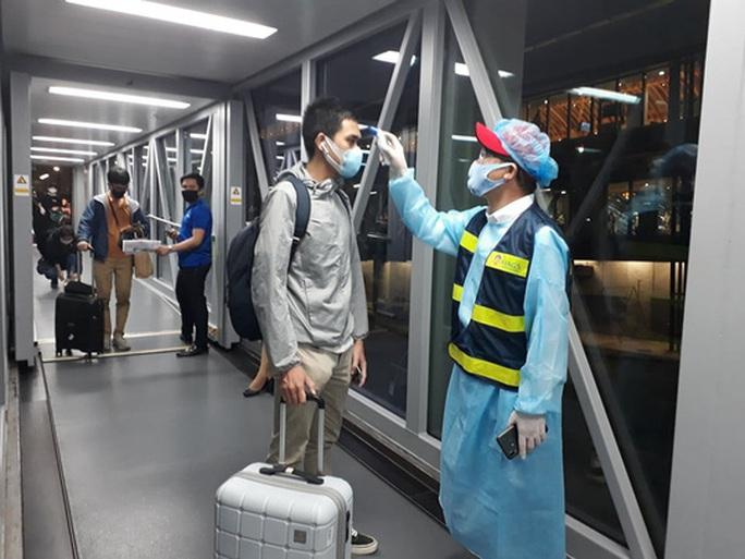 Từ vùng dịch nước ngoài về, hành khách vừa xuống máy bay liền được phun khử trùng toàn thân - Ảnh 1.