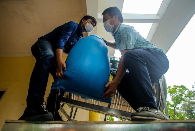 Người dân giãn cách 2 m nhận gạo từ cây ATM gạo đầu tiên ở Hà Nội - Ảnh 8.