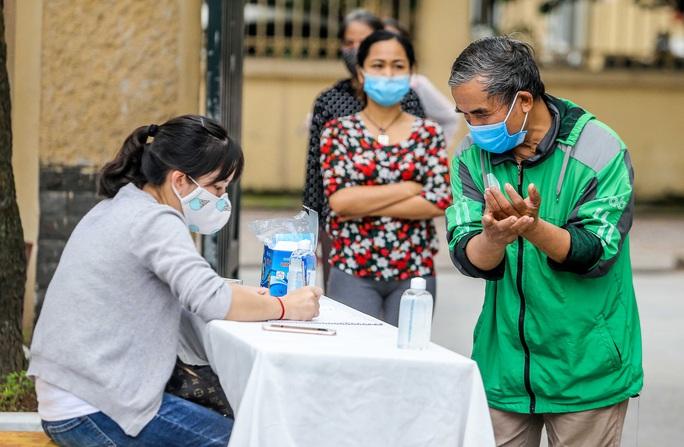 Người dân giãn cách 2 m nhận gạo từ cây ATM gạo đầu tiên ở Hà Nội - Ảnh 9.