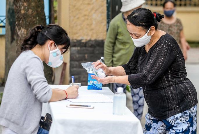 Người dân giãn cách 2 m nhận gạo từ cây ATM gạo đầu tiên ở Hà Nội - Ảnh 10.