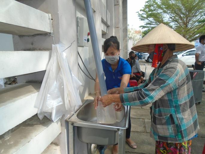 Hình 2 Sau khi đưa phiếu để kiểm tra, bà con chỉ cần ấn nút để nhận mỗi phần 2kg gạo