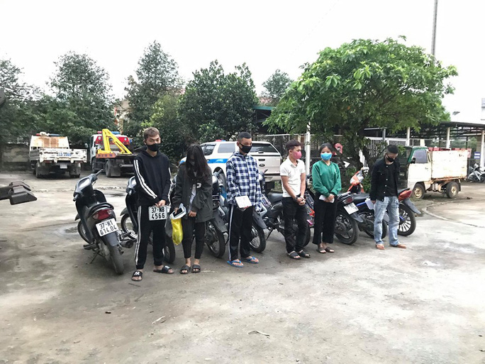 Bất chấp lệnh cấm, nhóm nam nữ thanh niên đi xe máy dàn hàng ngang, lạng lách - Ảnh 1.