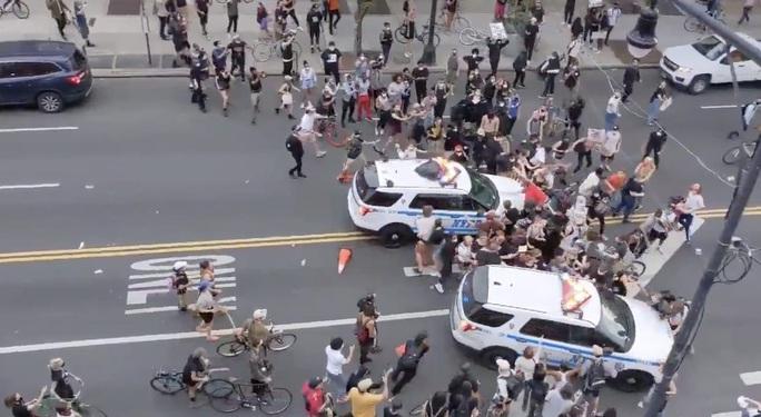 Biểu tình bạo lực ở Mỹ: Xe cảnh sát vượt rào tông vào đám đông - Ảnh 1.