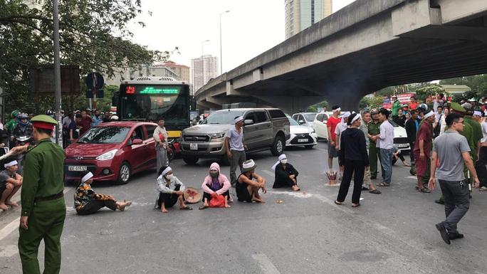 Hàng chục người mang di ảnh người thân bị tai nạn giao thông ngồi dàn hàng ngang ra đường - Ảnh 1.