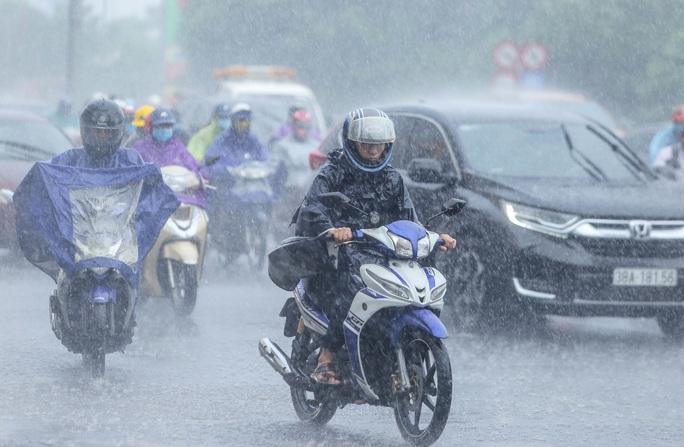 Người dân túm tụm dưới chân cầu vượt trong trận mưa vàng - Ảnh 1.