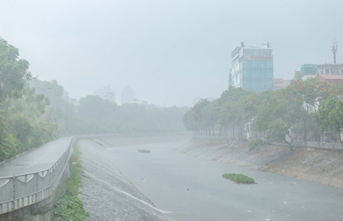 Người dân túm tụm dưới chân cầu vượt trong trận mưa vàng - Ảnh 13.