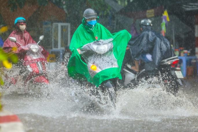 Người dân túm tụm dưới chân cầu vượt trong trận mưa vàng - Ảnh 14.