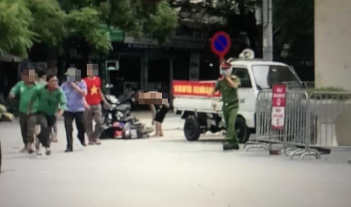 CLIP: Có mặt công an, người mặc áo Grab vẫn đuổi chém 2 tài xế xe ôm bị thương - Ảnh 2.