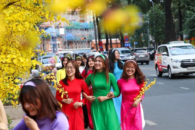 Người dân TP HCM xúng xính áo dài xuống phố du Xuân sớm - Ảnh 3.