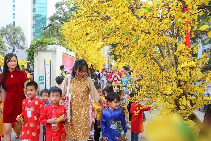 Người dân TP HCM xúng xính áo dài xuống phố du Xuân sớm - Ảnh 7.