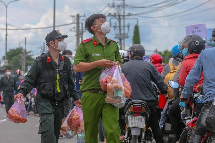 Quân đội, công an tặng thực phẩm, nước uống cho người dân trước khi rời TP HCM về quê - Ảnh 2.