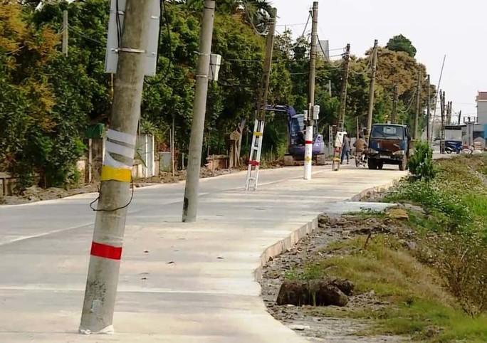 Hơn 40 cột điện mọc giữa đường giăng bẫy người đi đường đã được di dời - Ảnh 1.