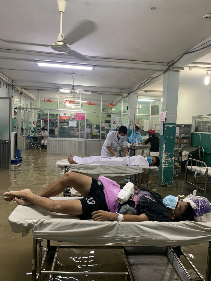 TP HCM: Bác sĩ xắn quần, lội nước bì bõm cấp cứu người bệnh - Ảnh 1.
