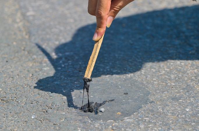 Cận cảnh mặt đường chảy nhựa dưới cái nắng nóng gay gắt - Ảnh 7.