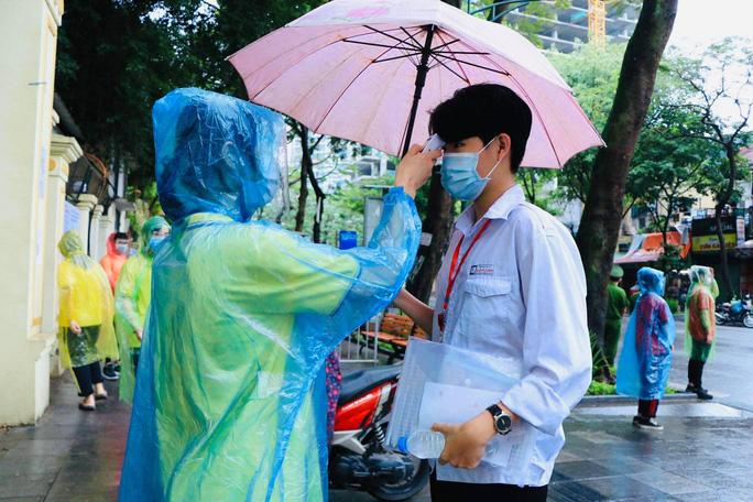 Thí sinh ướt áo vì mưa lớn, giáo viên nhắn bố mẹ mang quần áo đến điểm thi - Ảnh 1.