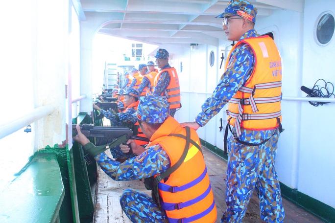 Cảnh sát biển trao cờ Tổ quốc và huấn luyện bắn súng pháo trên biển - Ảnh 1.