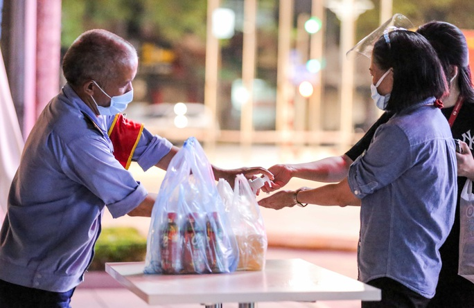 Người dân mặc áo mưa tiếp tế lương thực vào trung tâm thương mại bị phong toả - Ảnh 16.