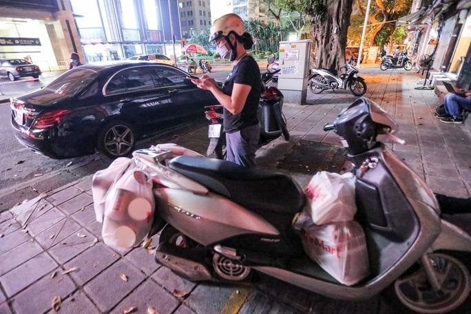 Người dân mặc áo mưa tiếp tế lương thực vào trung tâm thương mại bị phong toả - Ảnh 9.